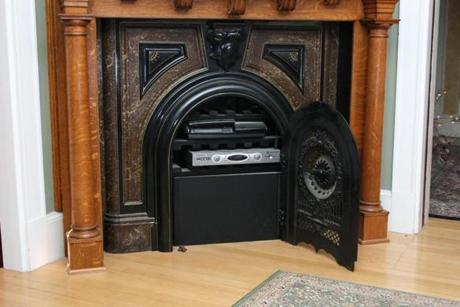 The 1880s stove inside a carved wooden mantel.